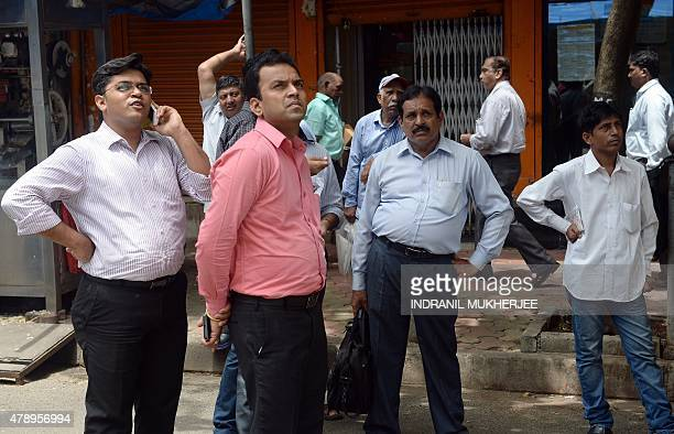 Indian bystanders outside the Bombay Stock Exchange watch stock prices on a digital broadcast during intraday trade in Mumbai on June 29 2015 Asian...