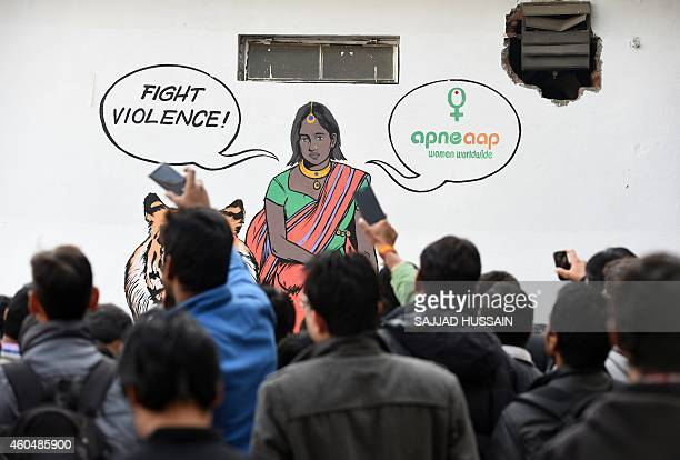 Indian bystanders watch a play by activists in front of a mural depicting fictional character Priya who is a rape survivor sitting on a tiger before...