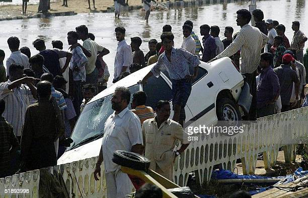 Indian bystanders watch rescue operations at the Marina beach in Madras 26 December 2004 after tidal waves hit the region throwing a car onto a road...