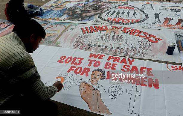 Indian bystanders write on a banner featuring images of 'government and rapists' as it lies on a road in New Delhi on January 1 2013 The family of an...