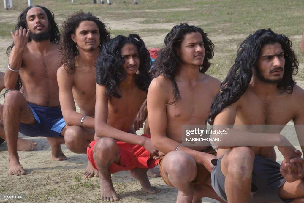 Indian candidates with long hair in a predominantly Sikh area where men traditionally never cut their hair wait to have their measurements taken...