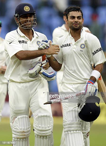 Indian captain and batsman MS Dhoni celebrates celebrates with his batting partner Virat Kohli after defeating New Zealand during the fourth day of...