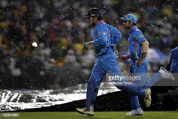 Indian Captain MS Dhoni and Virat Kohli run to the pavilion as sudden rain stopped the game during the ICC T20 World Cup Super Eight group 2 cricket...