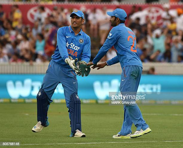 Indian captain MS Dhoni congratulates Gurkeerat Mann on his catch during the fourth oneday international cricket match between India and Australia at...