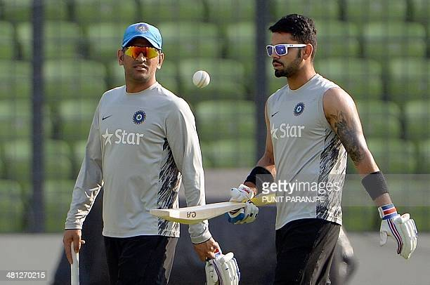 Indian captain Mahendra Singh Dhoni and teammate Virat Kohli arrive for a training session at The ShereBangla National Cricket Stadium in Dhaka on...