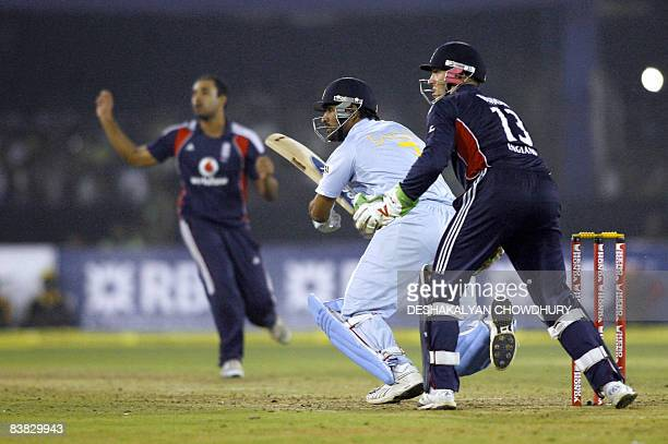 Indian captain Mahendra Singh Dhoni takes a short run watched by England wicket keeper Matt Prior and Owais Shah during the fifth One-Day...
