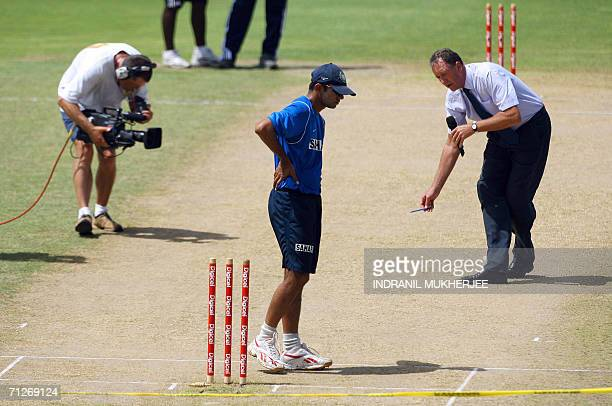 Indian captain Rahul Dravid inspects the pitch as former New Zealand captain and TV commentator Jeremy Coney does a pitch report after an inspection...