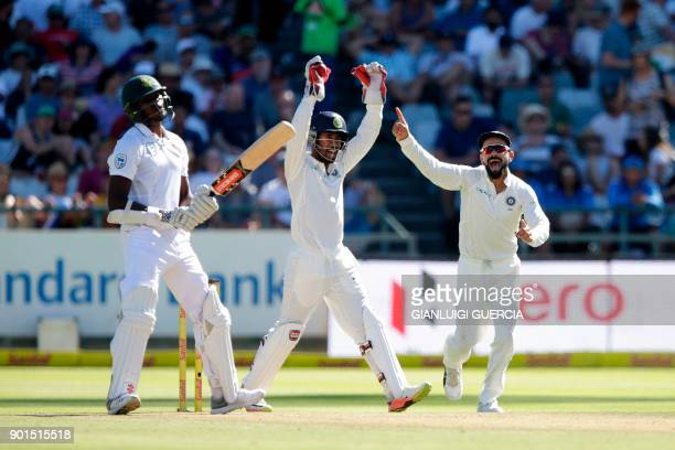 Indian captain Virat Kohli and wicket keeper Wriddhiman Saha celebrate the dismissal of South African batsman Kagiso Rabada on the first day of the...