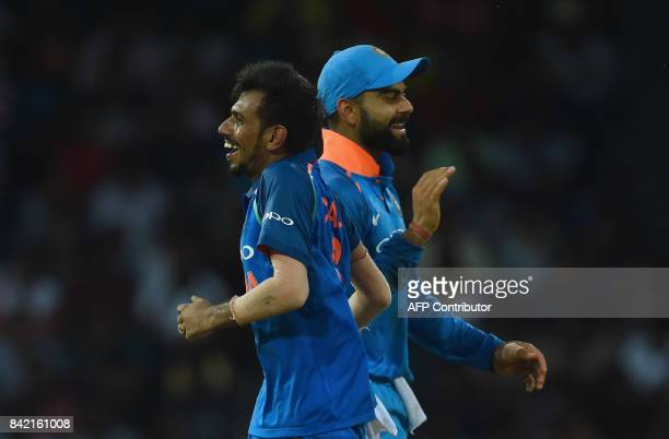 Indian captain Virat Kohli celebrates with his teammates Yuzvendra Chahal after he dismissed Sri Lankan cricketer Wanindu Hasaranga during the final...