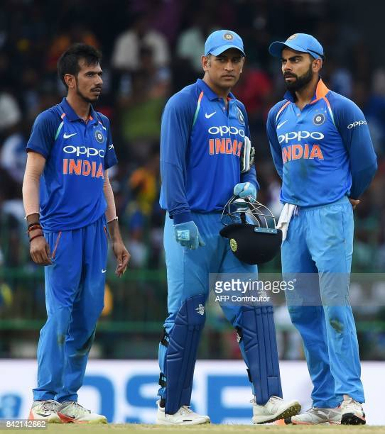 Indian captain Virat Kohli chats with wicketkeeper Mahendra Singh Dhoni and Yuzvendra Chahal during the final one day international cricket match...