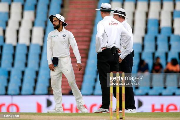 Indian Captain Virat Kohli reacts as umpires suspend play due to bad light during the third day of the second Test cricket match between South Africa...