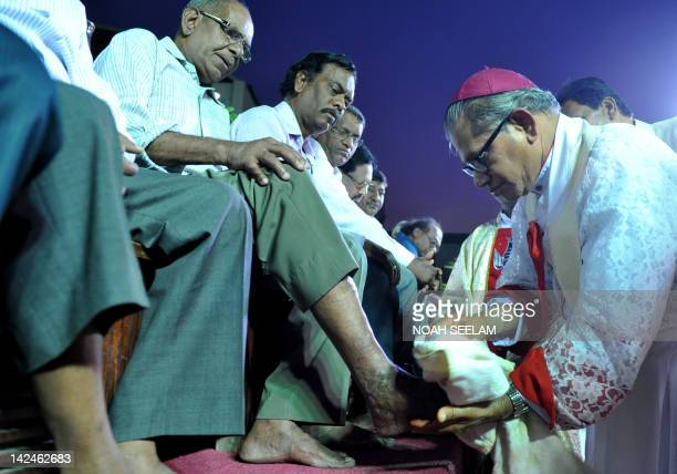 Indian Catholic Bishop Archdioecese of Hyderabad Reverend Thumma Bala washes the feet of a parishioner during the evening mass of the Lord Supper...