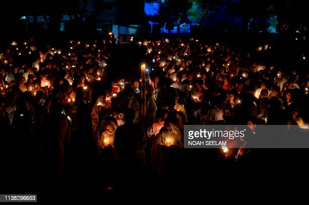 Indian Catholic Bishop of Archdiocese of Hyderabad Reverend Thumma Bala and priests walk with candles towards the altar as devotees attend a midnight...