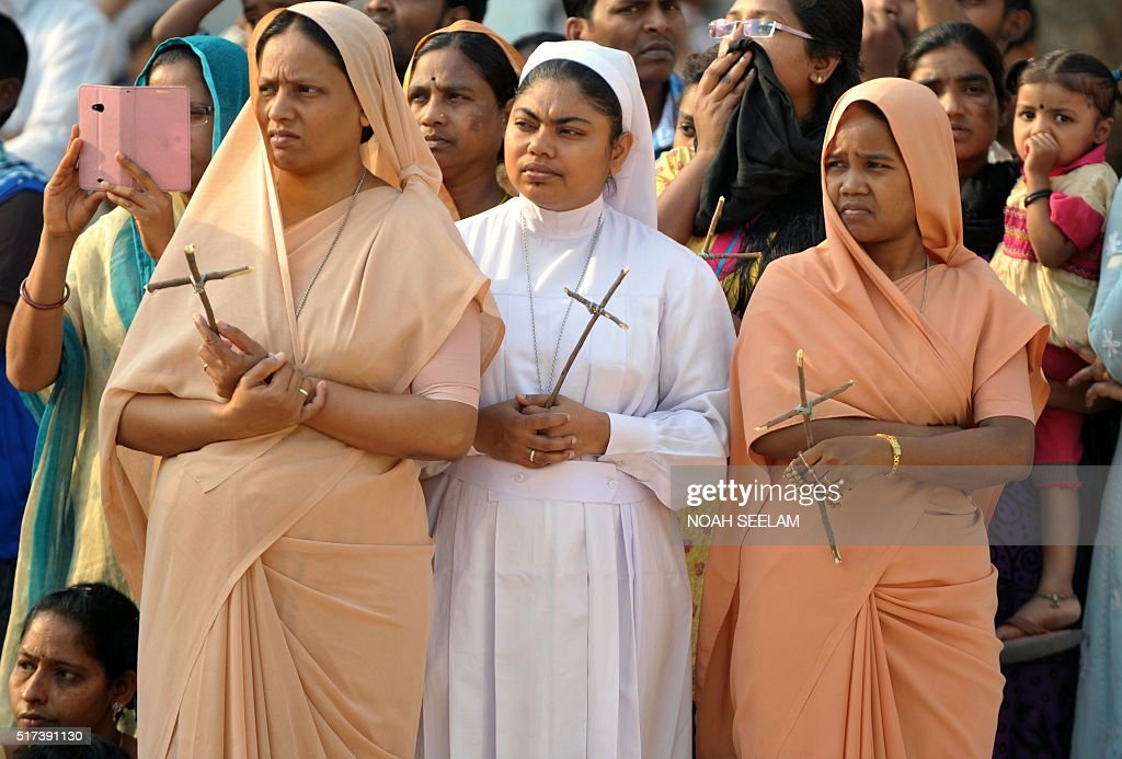 Indian Catholic nuns watch a re-enactment of the crucifixion