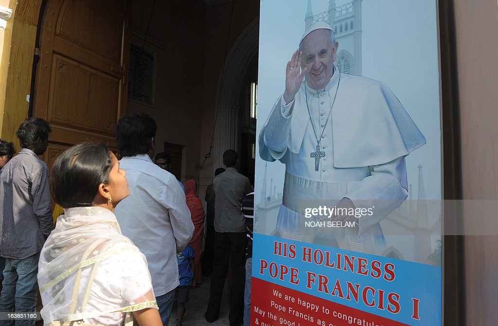 Indian Catholic's look at a poster of Pope Francis at Saint Mary's Basilica in Secunderabad the twin city of Hyderabad on March 17, 2013. The son of an Italian emigrant railway worker, Francis is a moderate conservative who is unlikely to change key doctrine but experts say that he could push for more social justice and a friendlier faith. AFP PHOTO / Noah SEELAM