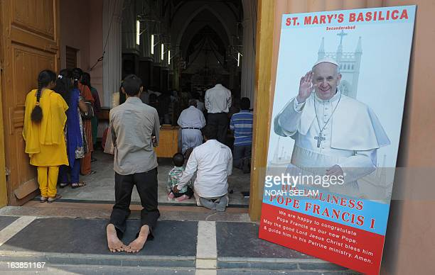 Indian Catholic's pray during a mass near a poster of Pope Francis at Saint Mary's Basilica in Secunderabad the twin city of Hyderabad on March 17...