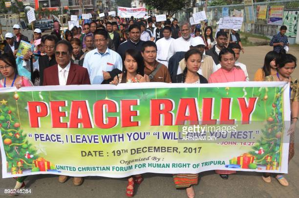 Indian Catholics volunteers of United Christian Forum for Human Rights of Tripura hold a banner during a peace rally for preChristmas celebrations in...