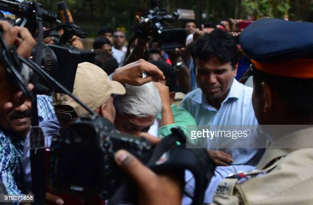 Indian Central Bureau of Investigation officials escort Gokulnath Shetty the former deputy manager of the Punjab National Bank into a special CBI...