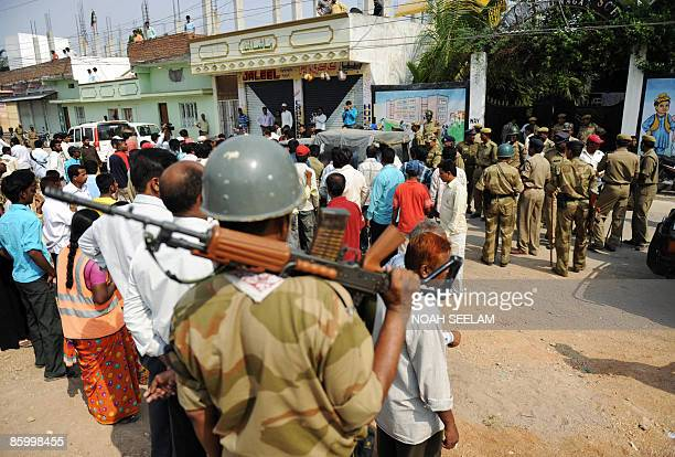 Indian Central Industrial Security Force paramilitary personnel look on as people crowd around the vehicle of Member of Legislative Assembly...