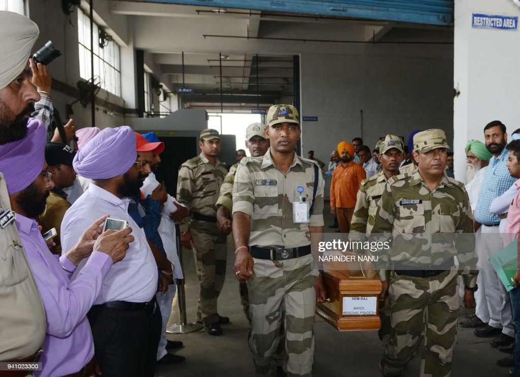 Indian Central Industrial Security Force personnel carry the coffin of Indian citizen Hemraj who was killed in Iraq at the International Airport in...