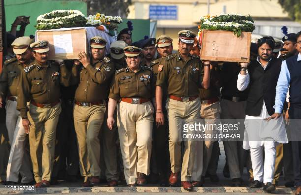 Indian Central Reserve Police Force personnel carry the coffins of colleagues Sudip Biswas and Bablu Santra at the Kolkata airport on February 16...