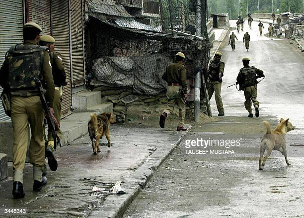 Indian Central Reserve Police Force personnels run along a deserted street following a blast in Baramulla some 55 Kms northwest of Srinagar 20 April...