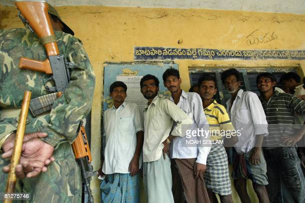 Indian Central Reserve police personnel stand guard as villagers wait in line to cast their votes in a local byelection at the village of...