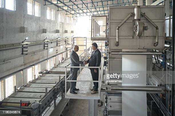 indian ceo and senior manager in mumbai textile factory - industrial equipment stock pictures, royalty-free photos & images