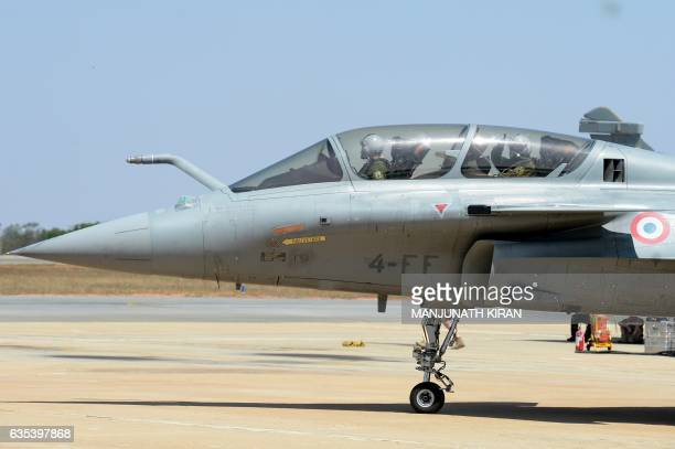 Indian Chairman of the Anil Dhirubhai Ambani Group Anil Ambani gestures from the cockpit of a Rafale fighter jet built by French aviation...