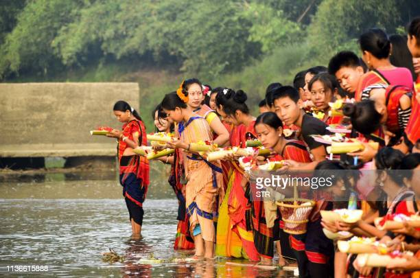 Indian Chakma Indigenous women and youth leave flowers in the Dew River during the 'Biju' festival at Pecharthal in Unakoti district in the...