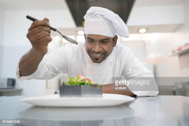 インドのシェフが非常に幸せそうに見えてサラダにドレッシングを追加します。