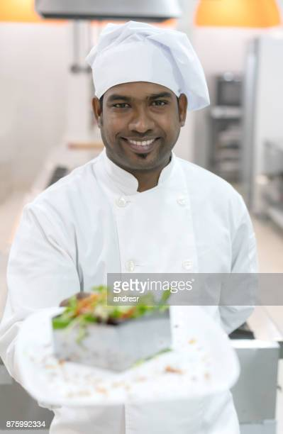 Indian chef looking at camera while holding a salad he just made