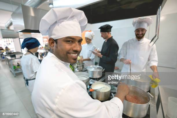 Indian chef looking at the camera smiling while mixing a hot sauce on the stove