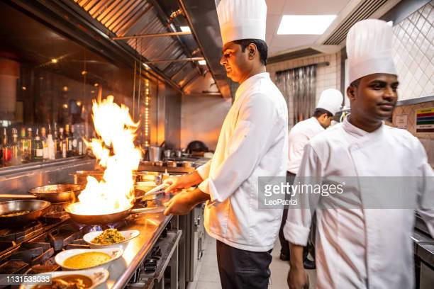 indian chefs cooking in a professional kitchen of a gourmet restaurant - indian food stock pictures, royalty-free photos & images