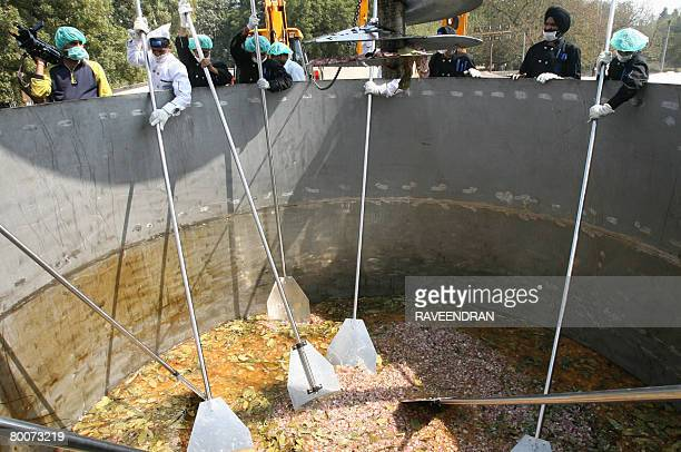 Indian chefs uses outsize ladles as they prepare a huge version of the popular South Asian 'Biryani' dish in New Delhi on March 1 2008 The marathon...