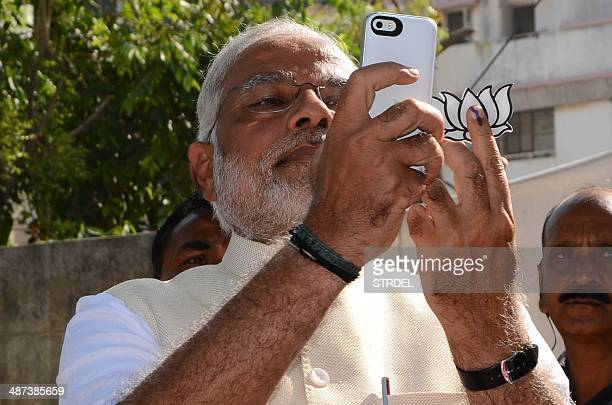 Indian Chief Minister for the western state of Gujarat and Bharatiya Janta Party prime ministerial candidate Narendra Modi takes a 'selfie' after...