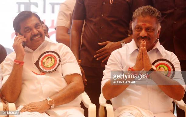 Indian Chief Minister of the state of Tamil Nadu Edappadi Palanisamy uses a cellphone as as Deputy Chief Minister O Pannerselvam gestures to members...