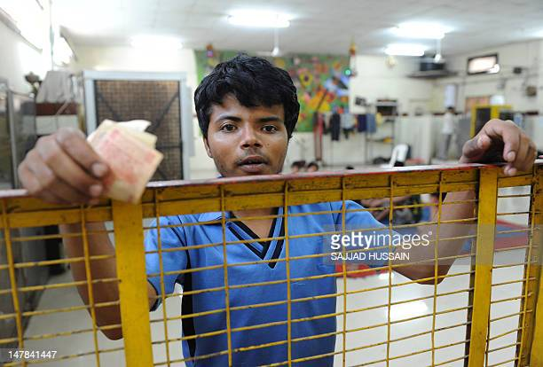 Indian child labourer Ram Singh stands at the children's Development Khazana counter to deposit his money at a children's bank after he finished his...