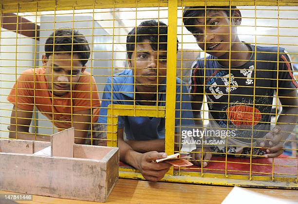 Indian child labourer Ram Singh waits at the children's Development Khazana counter to deposit his money at a children's bank after he finished his...