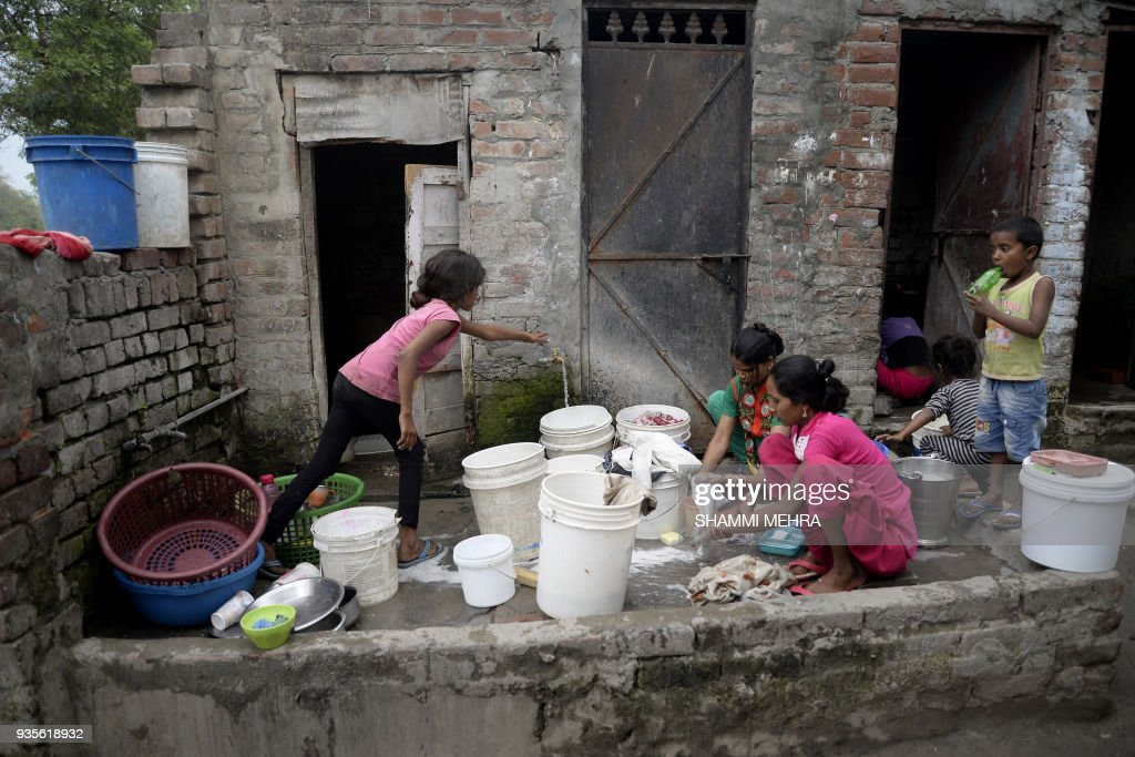 Indian child Radha uses a tap dispensing drinking water outside houses in Jalandhar on March 21 2018 World Water Day is observed on March 22 and...