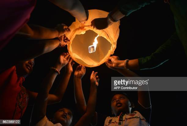 Indian children along with volunteers of a street dog organisation release sky lanterns to promote a peaceful and ecofriendly Diwali and create...
