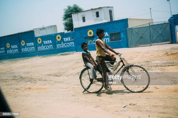 Indian children are riding bicycle in rural area