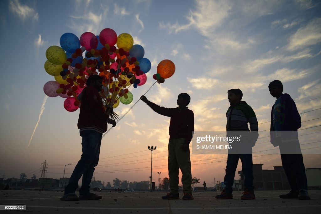 TOPSHOT Indian children buy balloons from a street vendor in Jalandhar on January 10 2018 / AFP PHOTO / Shammi MEHRA