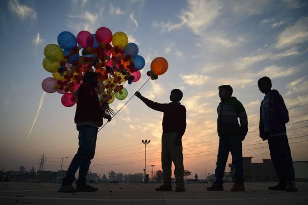 TOPSHOT Indian children buy balloons from a street vendor in Jalandhar on January 10 2018 / AFP PHOTO / Shammi MEHRA