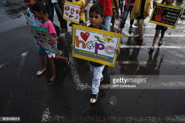 Indian children cross a road with posters in their hands to promote awareness about organ donation in Kolkata on July 27 2017 / AFP PHOTO /...