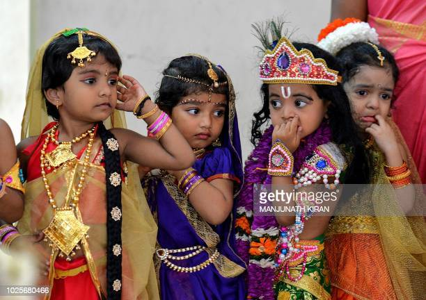 Indian children dressed as the Hindu deity Krishna and his cosort Radha wait in line to participate in a fancy dress competition held as part of...