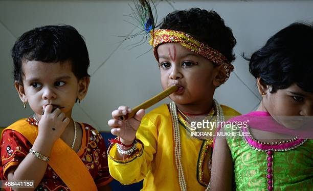 Indian children dressed as the Hindu God Lord Krishna smiles during an event in a school on the eve of 'Janmashtami' which marks Krishna's birth in...