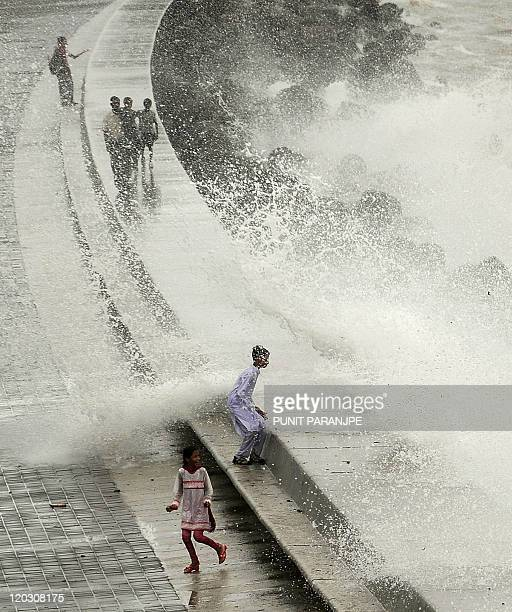 Indian children enjoy splash of high tide waves at the sea front in Mumbai on July 16 2011 India has forecast a 'normal' monsoon this year that could...