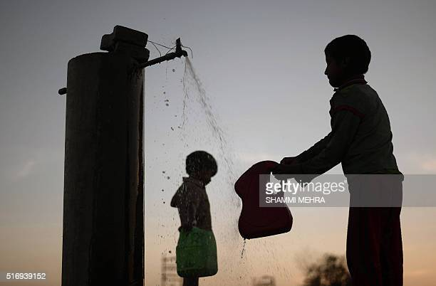Indian children fill containers with water from a tap on World Water Day in Jalandhar on March 22 2016 International World Water Day is marked...