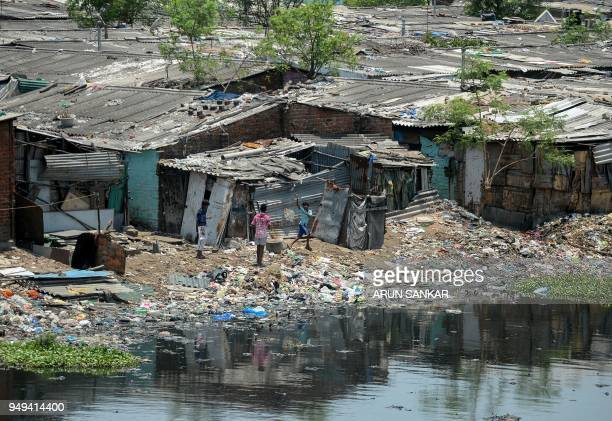 TOPSHOT Indian children fly kites on the banks of the polluted Cooum River next to homes in Chennai on April 21 2018 April 22 is observed as Earth...